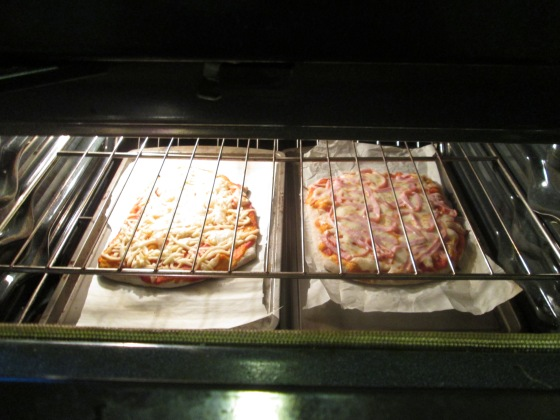 First round of pizzas in the oven! Non dairy cheese on the left, mozzarella and turkey ham on the right